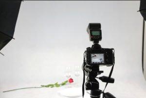 Aparat robiący zdjęcie róży na białym tle