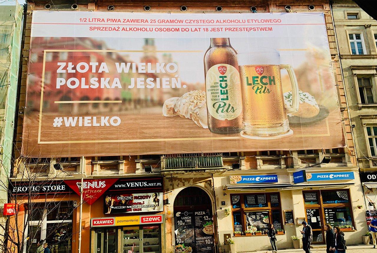 Reklama piwa przy ruchliwym chodniku