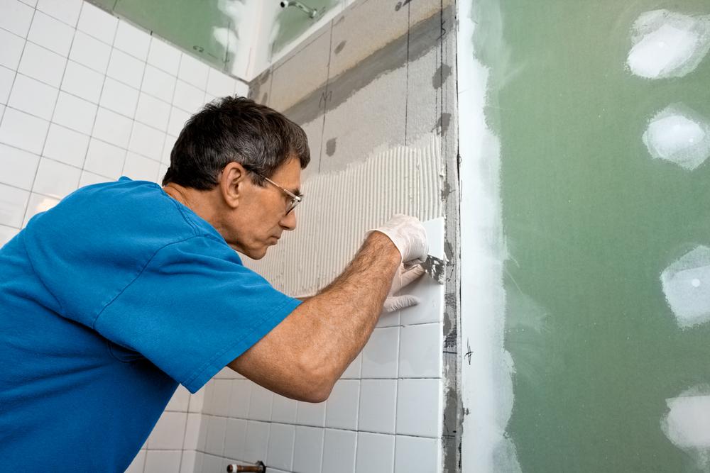 Pracownik kładzący płytki - remont łazienki
